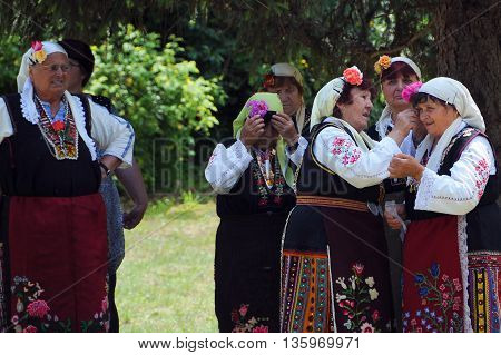 ARBANASI VILLAGE BULGARIA - JUNE 5 2016: Aged Bulgarian women get ready for performance at the National Folk Festival