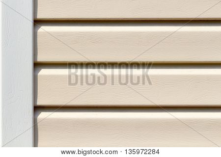 The surface of the beige plastic siding close up as a background
