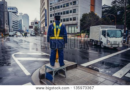 Tokyo Japan - February 26 2015: Security officer stands on stool on Sotobori Street in Akasaka area of Tokyo