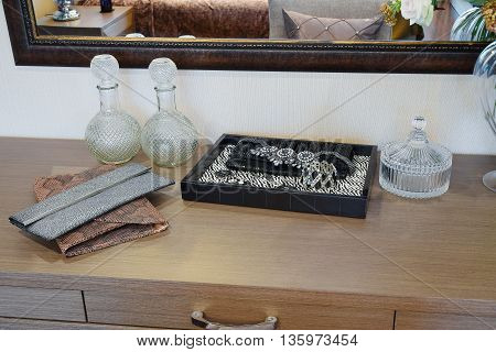 Handbag And Jewelry Set On A Dresser Table In A Contemporary Room.