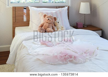 White Bedroom Decorative With Girl Dress, Pillows And Dolls On Bed