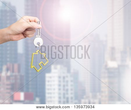 Hand Holding Key Ring In House Shape With City Building Background, 3D Rendering