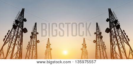 Silhouette, telecommunication towers with TV antennas and satellite dish in sunset, panorama composition