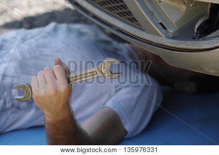 A driver lying under a car with a wrench in his hand outdoor cropped shot with selective focus
