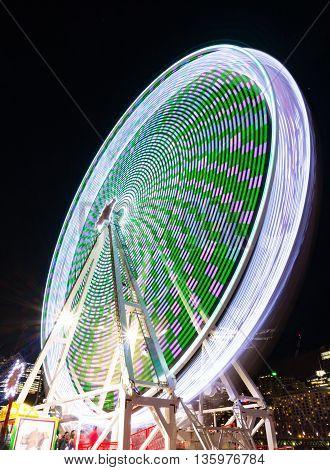 Amusement park attractions. Spinning ferris wheel at night. Motion blur