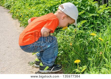 A little boy in an orange shirt and jeans smelling a yellow dandelion flower in the park