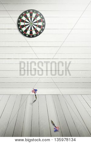 Darts board on wooden wall and darts miss the target drop on the ground.