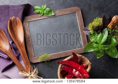 Blackboard for your text, fresh garden herbs in mortar, chili pepper and olive oil on stone table. Basil, rosemary, dill. Cooking ingredients. Top view with copy space
