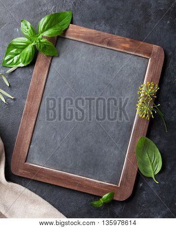 Blackboard for your text and fresh garden herbs on stone table. Basil, rosemary, dill. Cooking ingredients. Top view with copy space