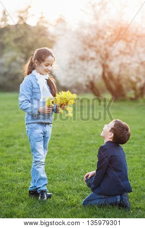 boy gave flowers to the girl and stood before her on his knee