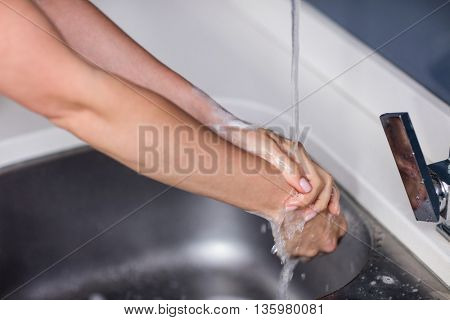 Cropped image of woman washing hands in washbasin at home