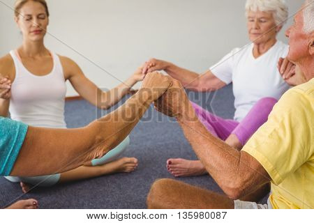 Concentrated seniors holding hands together in circle in fitness class