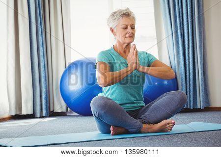 Portrait of senior woman sitting in lotus position in studio
