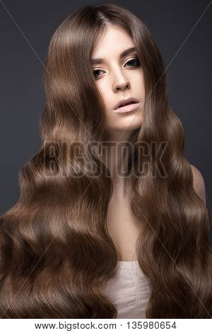 Beautiful brunette girl with a perfectly curls hair and classic make-up. Beauty face. Picture taken in the studio.