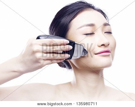 young asian woman using a face spa instrument isolated on white.