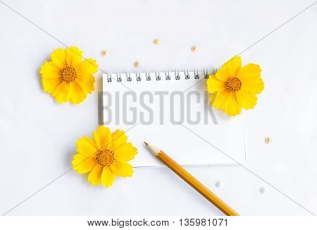 Blank notepad, brown pencil yellow flowers and beads on white background, space for text or message