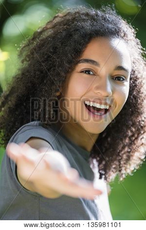 Outdoor portrait of beautiful happy mixed race African American girl teenager female young woman smiling with perfect teeth holding hand to camera