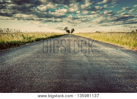 Empty straight long asphalt road. Dramatic cloudy sky. Concepts of travel, adventure, destination, transport etc. Vintage style