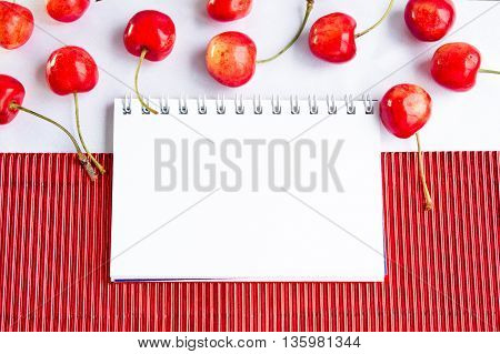 Blank spiral notepad and ripe cherries on  red corrugate cardboard paper and white tablecloth, space for text or message