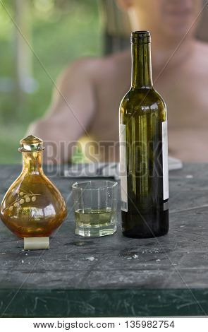 A bottle of white wine in focus and male sitting at the table in the blurred background. Concept of a pleasure of drinking wine in a good weather