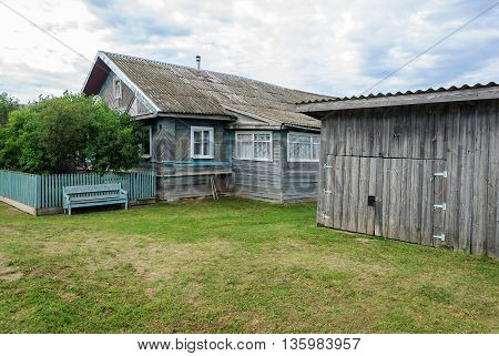 Old wooden house with shed and lawn in russian village summer day