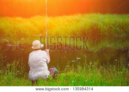 Elderly woman in a hat sitting on a chair with his back turned and caught the bait of bamboo fish in the river on a sunny summer day.