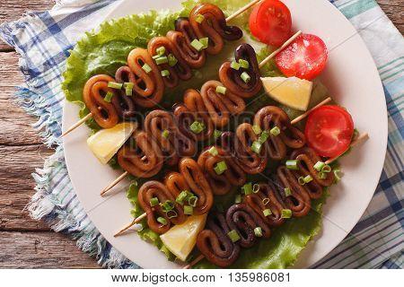 Kebab From Calamari On Skewers With Vegetables. Horizontal Top View