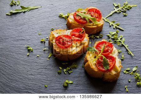 Toasts (Crostini) with ricotta cherry tomatoes and arugula on black background.