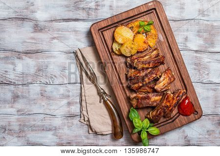 elicious Grilled Pork Rib and Fried Potato Wedges with Sauce on wooden cutting board, top view