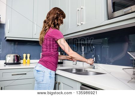 Side view of woman filling water in glass from faucet at kitchen counter