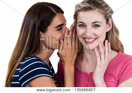 Smiling woman telling secret to friend while standing on white background