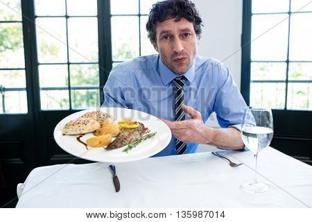 Portrait of frustrated man sitting at table and holding a plate of meal in restaurant