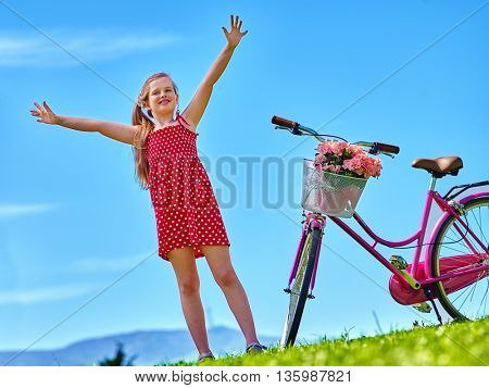 Bikes cycling girl. Child girl wearing red polka dots dress rides bicycle with flowers basket. Mountains and blu sky on background.