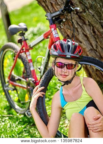Bikes cycling girl. Girl rides bicycle. Girl in cycling have a rest sitting under tree. Cycling is good for health. Cyclist looking at camera.