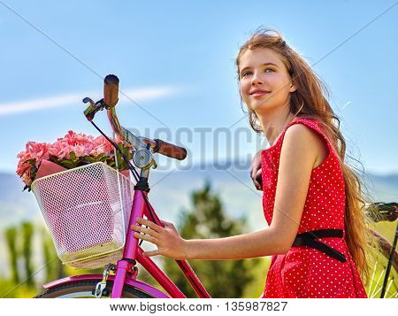 Bikes bicycle girl. Teenager girl wearing red polka dots dress looking camera keeps bicycle with flowers basket. Lot of green tree and blu sky in park.