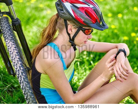 Bikes cycling girl. Bicyclist girl watch on smart watch. Girl counts pulse after bicycle training. Cycling is good for health.