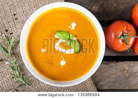 Tomato squash soup with basil leaf and sour cream