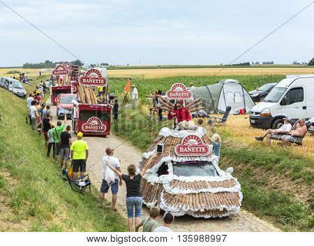 Quievy, France - July 07 2015: Banette caravan during the passing of the Publicity Caravan on a cobblestone road in the stage 4 of Le Tour de France on July 7 2015 in Quievy France. Banette is the leading brand for the artisan bread in France.