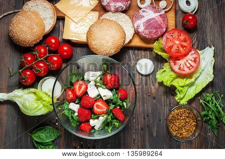 Ingredients for making homemade burger and salad with strawberries and tofu.