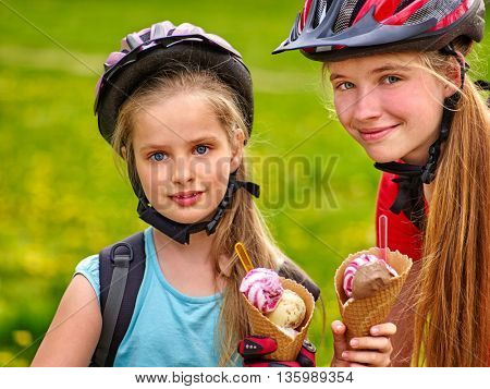 Bikes bicyclist girls. Girls wearing bicycle helmet with rucksack rides bicycle. Girls children are bicycling in summer park. Girls biking eating ice cream cone . Bicyclist is looking at each other.