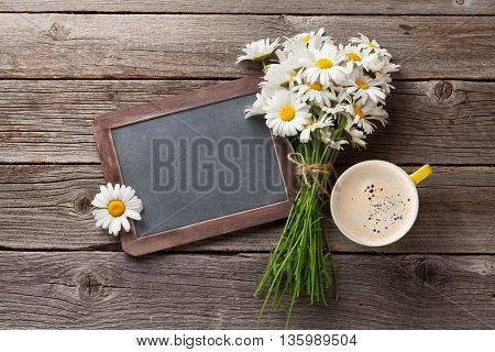 Blackboard for your text, flowers and coffee cup. Top view with copy space