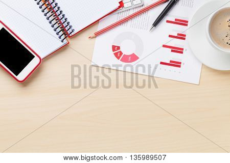 Office desk workplace with charts, coffee cup, pc, smartphone and notepad on wooden table. Top view with copy space