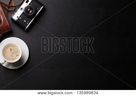 Office desk with photo camera and coffee cup. Top view with copy space