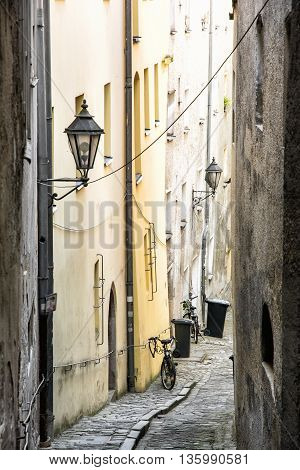 Narrow street with ancient houses in the old town Passau Germany Unesco. Architectural theme. Vertical composition. Travel destination. Stone pavement street lamps and bicycles.