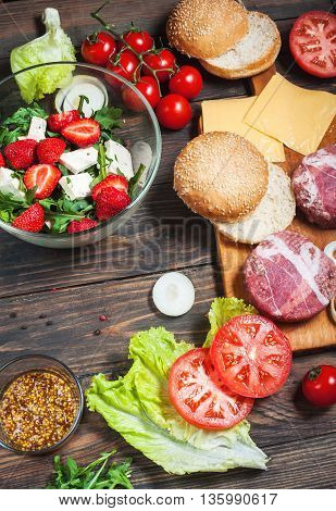 Ingredients for making homemade burger and salad with strawberries, tofu.