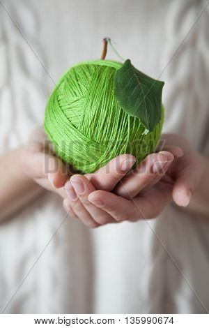 Ball of green wool in the form of an apple. Green apple of woolen thread. Hands holding a ball of wool. Light background. Knitted Sweater White.