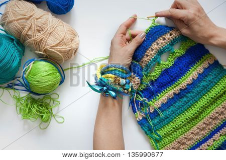 Knitted fabric of wool. Crochet. White background. View from above. Blue green aqua beige color. To crochet.
