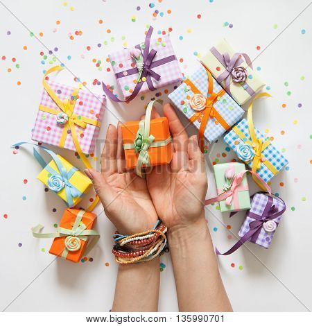 Female hand holding a small gift. Gift wrapped in paper. Small gifts are packed in colored paper. Colored ribbons.
