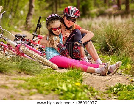 Bikes cycling family. Happy mother and daughter are sitting on road near bicycles. Cycle racing concept.