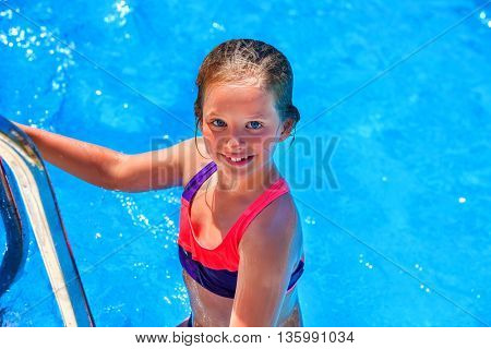 Child girl coming out of swimming pool . Pool steps on foreground. Summer holiday. Outdoor.